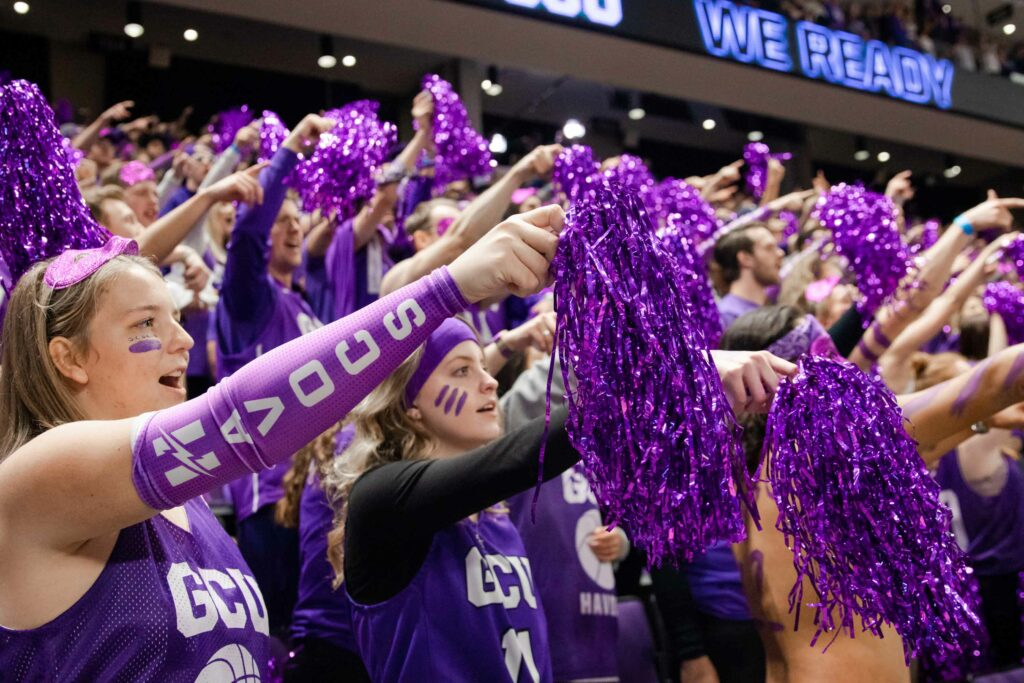 GCU Havocs pointing with purple pom poms